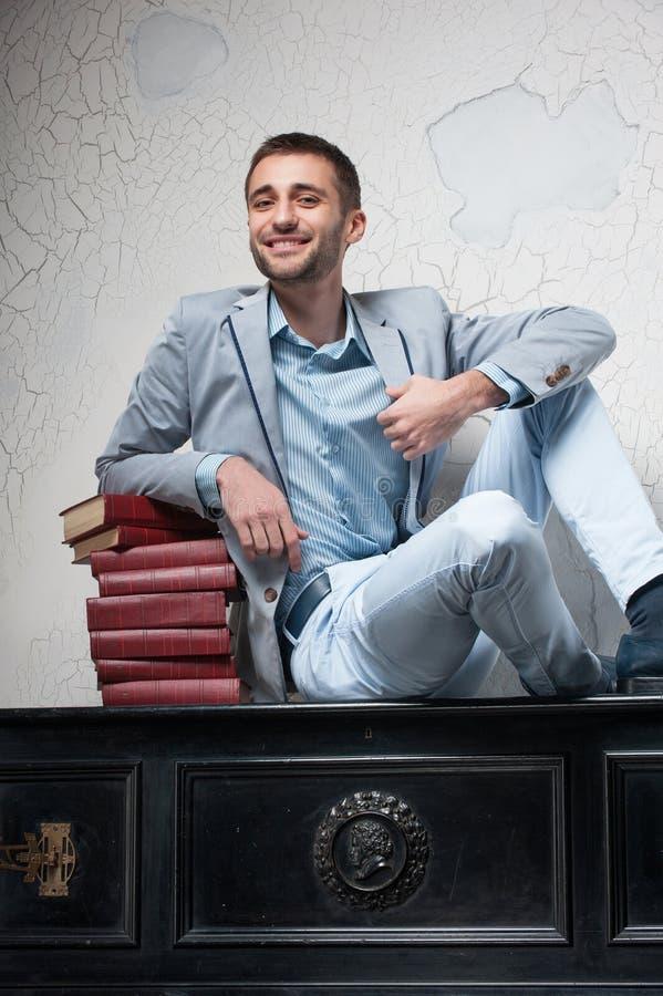 O homem novo com livros senta-se em um piano foto de stock royalty free
