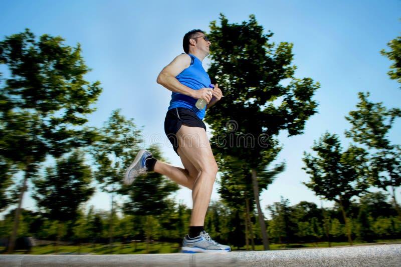 O homem novo com os pés atléticos do corredor que guardam a energia isotonic bebe ao correr no parque da cidade imagem de stock