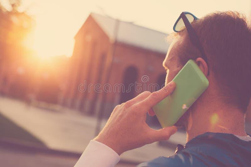 O homem novo com telefone celular tem uma conversação, por do sol na rua foto de stock royalty free