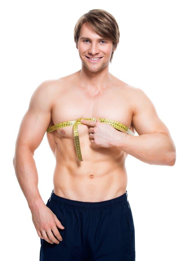 O homem novo com torso muscular usa a fita de medição imagens de stock royalty free
