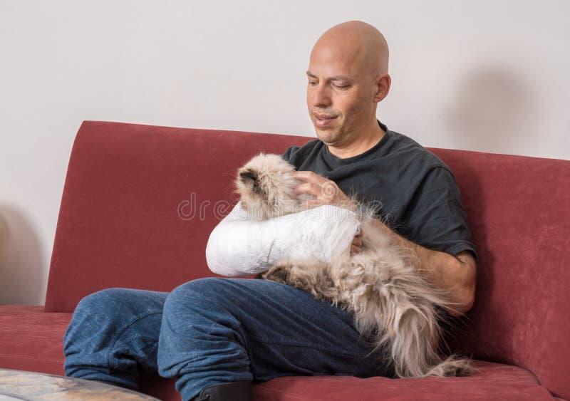 O homem novo com um braço moldou trocas de carícias seu gato fotografia de stock royalty free