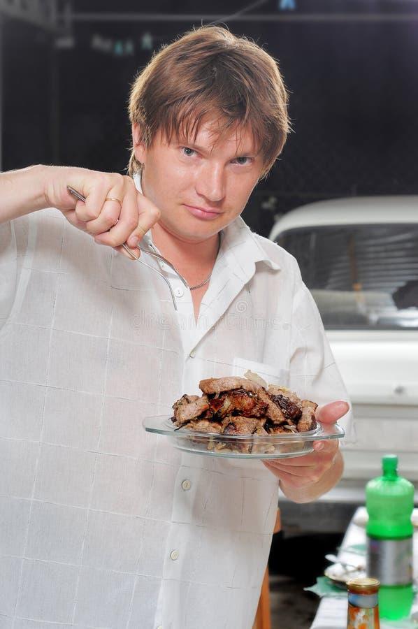 O homem novo com um kebab do shish. fotografia de stock