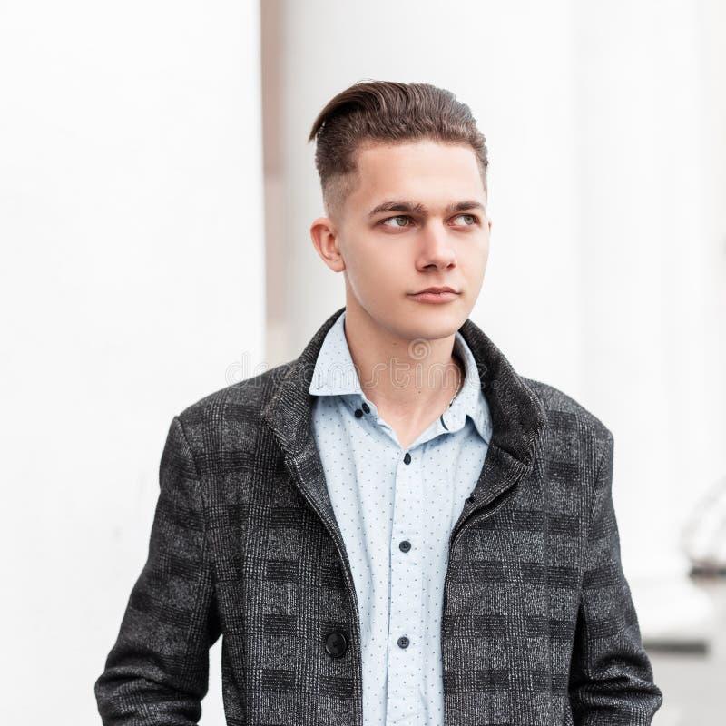 O homem novo considerável agradável em um revestimento elegante da manta cinzenta em uma camisa com um penteado à moda está perto imagem de stock