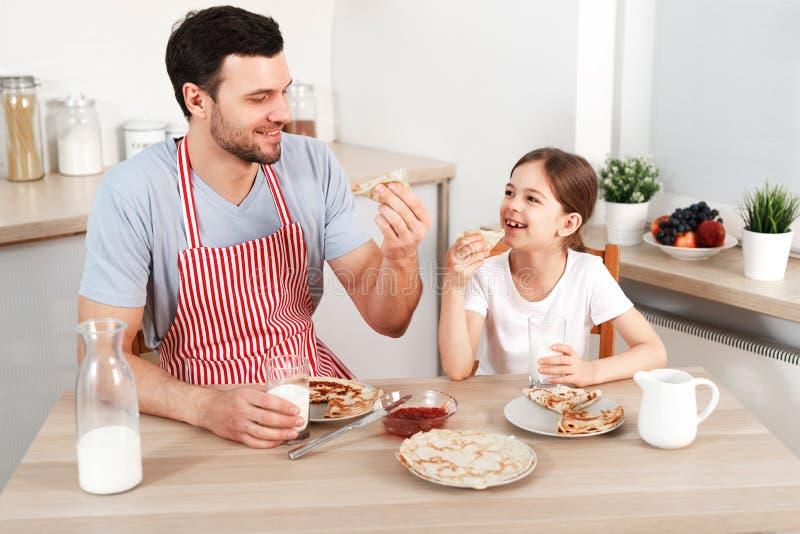 O homem novo considerável alegre e a criança pequena comem panquecas junto, leite fresco das bebidas, apreciam o café da manhã na foto de stock royalty free