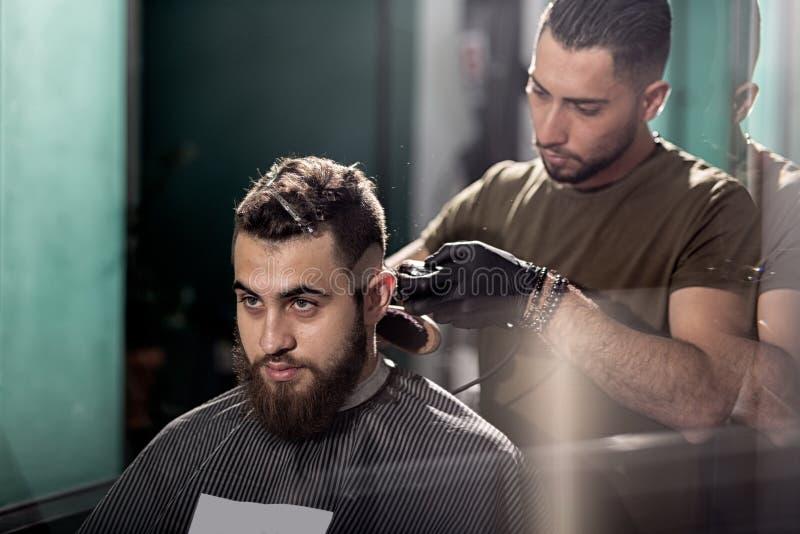 O homem novo considerável com barba senta-se em uma barbearia O barbeiro barbeia os cabelos na parte traseira imagens de stock royalty free