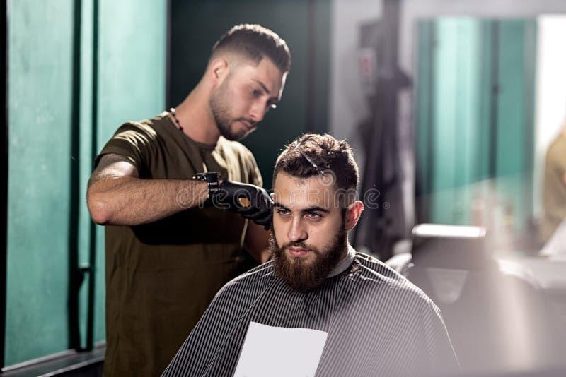 O homem novo considerável com barba senta-se em uma barbearia O barbeiro barbeia os cabelos no lado imagem de stock