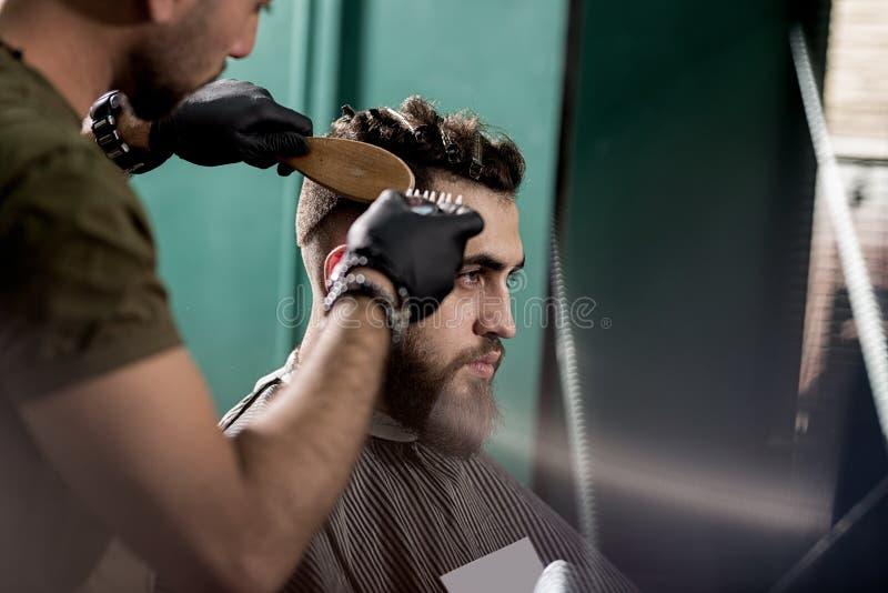 O homem novo considerável com barba senta-se em uma barbearia O barbeiro em luvas pretas barbeia os cabelos no lado imagens de stock