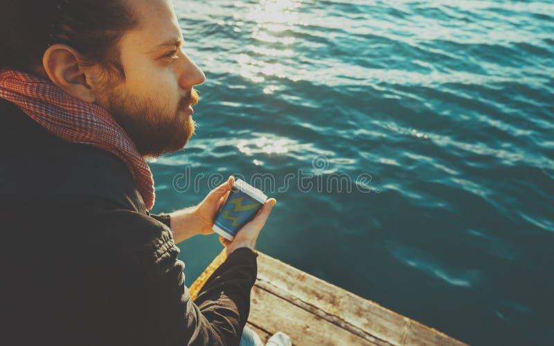 O homem novo considerável com um vidro do café senta-se à disposição em Pier And Enjoys Sea View fotos de stock royalty free