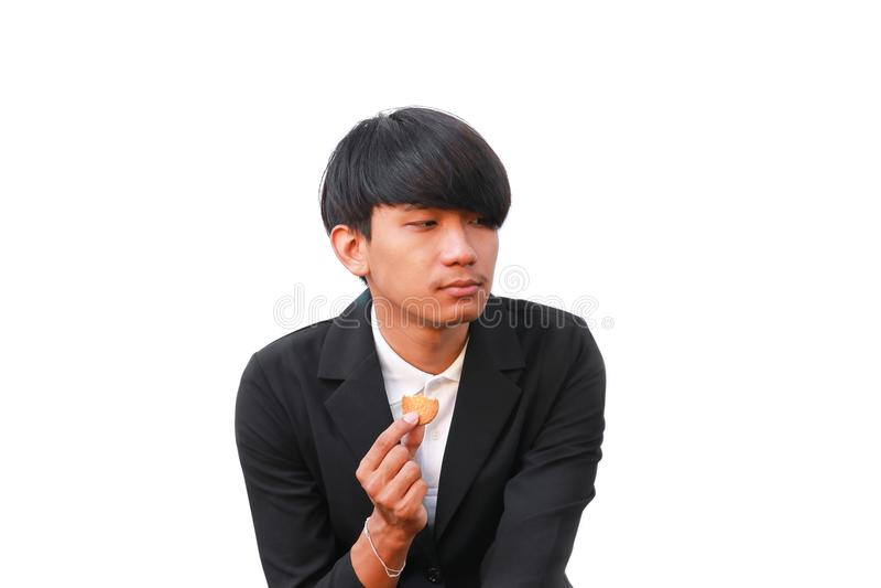 O homem novo considerável come a cookie partes pequenas no fundo branco foto de stock royalty free