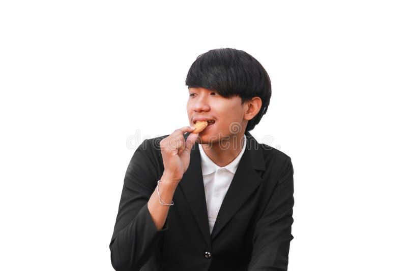 O homem novo considerável come a cookie partes pequenas no fundo branco fotos de stock