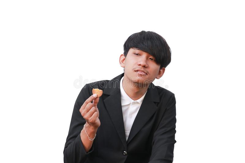 O homem novo considerável come a cookie partes pequenas no fundo branco imagens de stock
