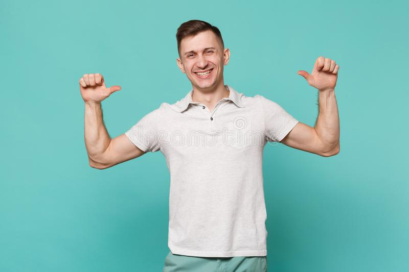O homem novo considerável de sorriso em estar da roupa ocasional, apontando os polegares nsi mesmo isolou-se na parede azul de tu foto de stock