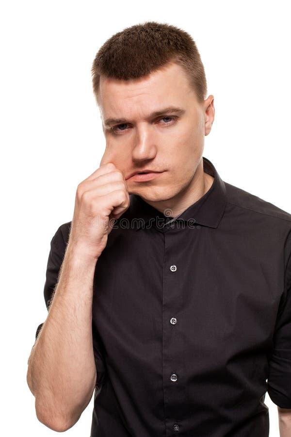 O homem novo considerável em uma camisa preta está fazendo as caras, ao estar isolado em um fundo branco fotos de stock royalty free
