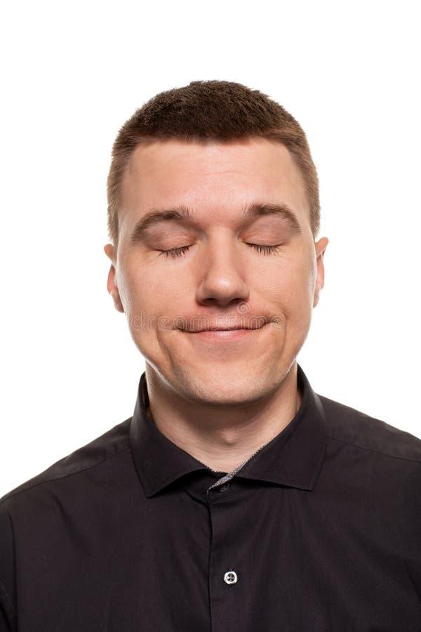 O homem novo considerável em uma camisa preta está fazendo as caras, ao estar isolado em um fundo branco foto de stock royalty free