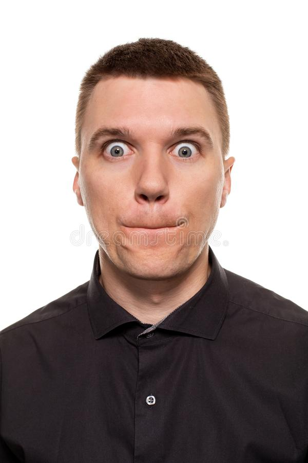 O homem novo considerável em uma camisa preta está fazendo as caras, ao estar isolado em um fundo branco fotografia de stock royalty free