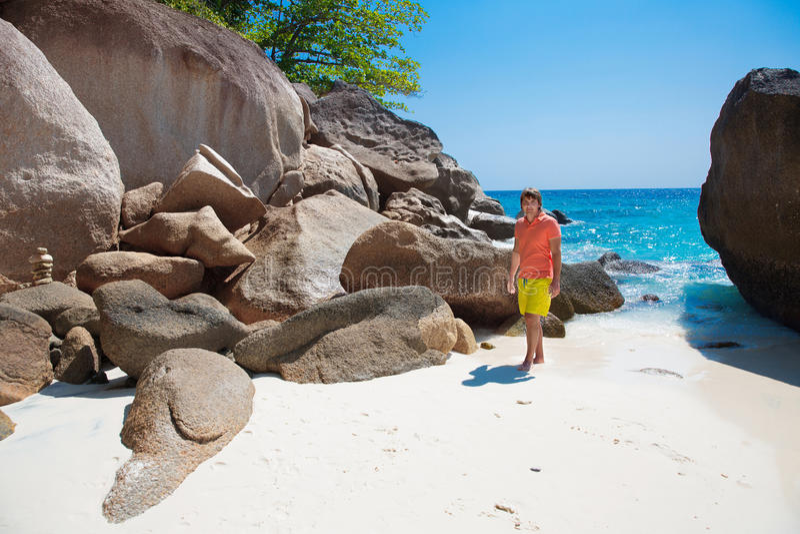 O homem novo considerável em uma praia tropical, relaxa em férias de verão foto de stock royalty free