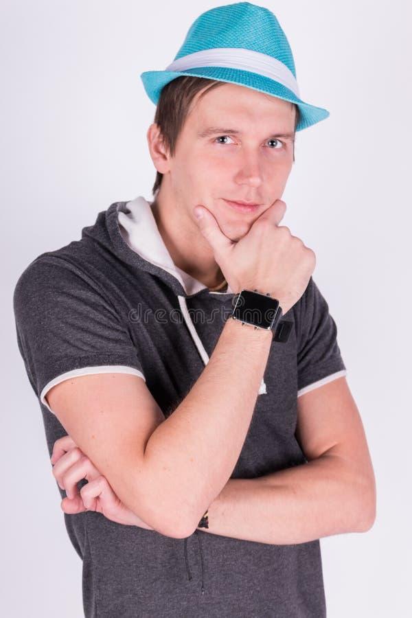 O homem novo considerável encantador no formalwear guarda um fundo azul do branco do chapéu imagens de stock