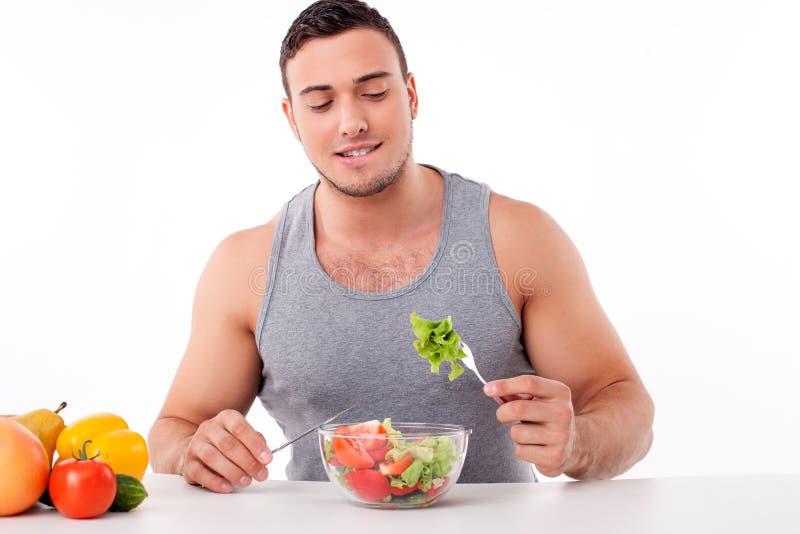 O homem novo considerável está comendo o alimento saudável fotografia de stock royalty free