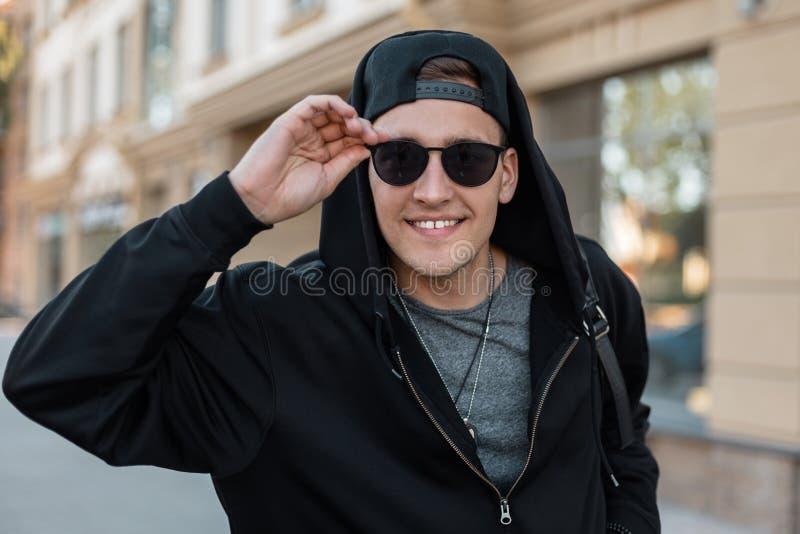 O homem novo considerável feliz do moderno em óculos de sol à moda em uma camiseta elegante com uma trouxa em um tampão está esta imagens de stock