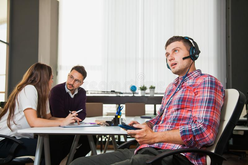 O homem novo considerável nos fones de ouvido guarda a tabuleta digital no escritório para negócios imagem de stock