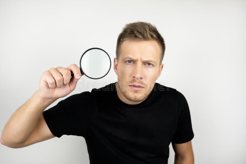O homem novo considerável que veste a lupa preta da terra arrendada do t-shirt perto de seu olho olha o branco isolado suspeito imagens de stock
