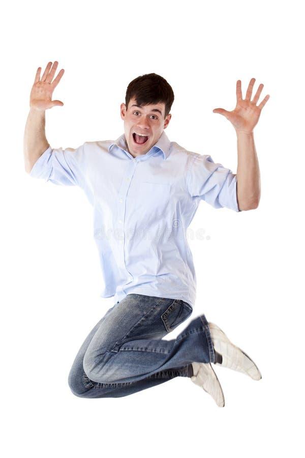 O homem novo considerável salta no ar fora da alegria foto de stock