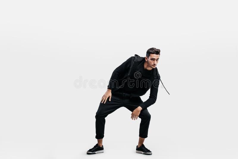 O homem novo considerável vestido na roupa de um preto do esporte está dançando a dança da rua foto de stock royalty free