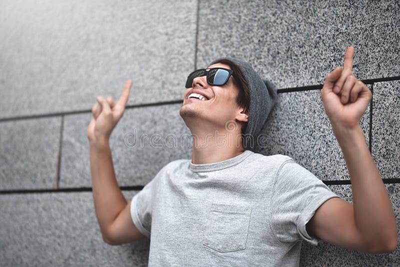O homem novo consider?vel com ?culos de sol est? apontando afastado, olhar acima e sorrir, estando contra a parede cinzenta imagens de stock
