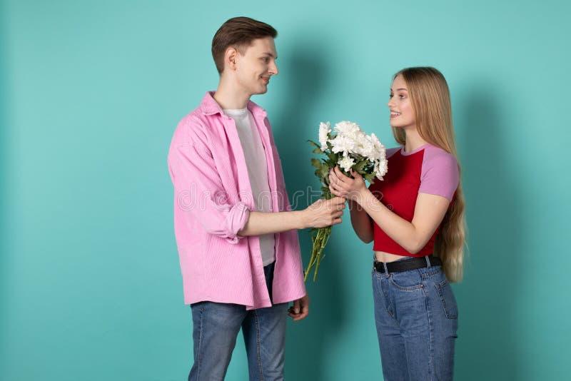 O homem novo consider?vel na camisa cor-de-rosa d? um ramalhete das flores brancas a sua amiga loura bonita fotos de stock