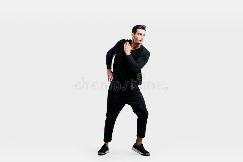 O homem novo consider?vel vestido na roupa de um preto do esporte est? dan?ando a dan?a da rua imagens de stock royalty free