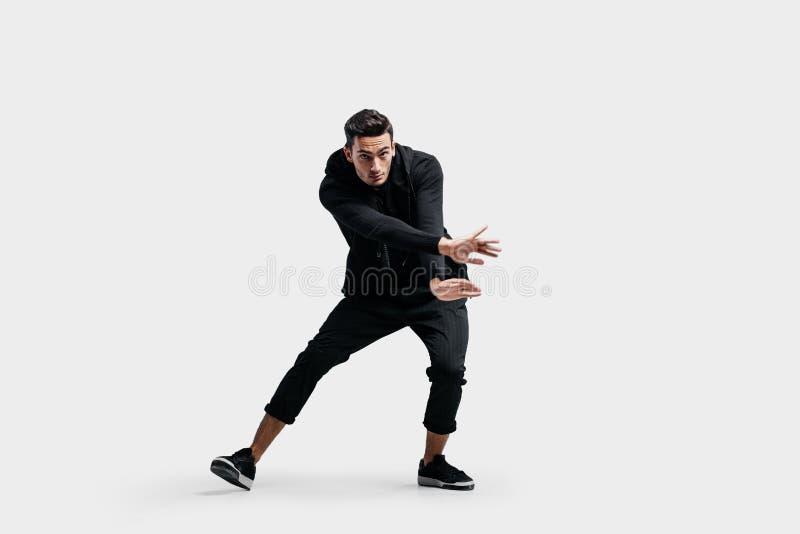 O homem novo consider?vel vestido no roupa preta est? dan?ando a dan?a da rua Faz movimentos estilizados com suas m?os imagens de stock