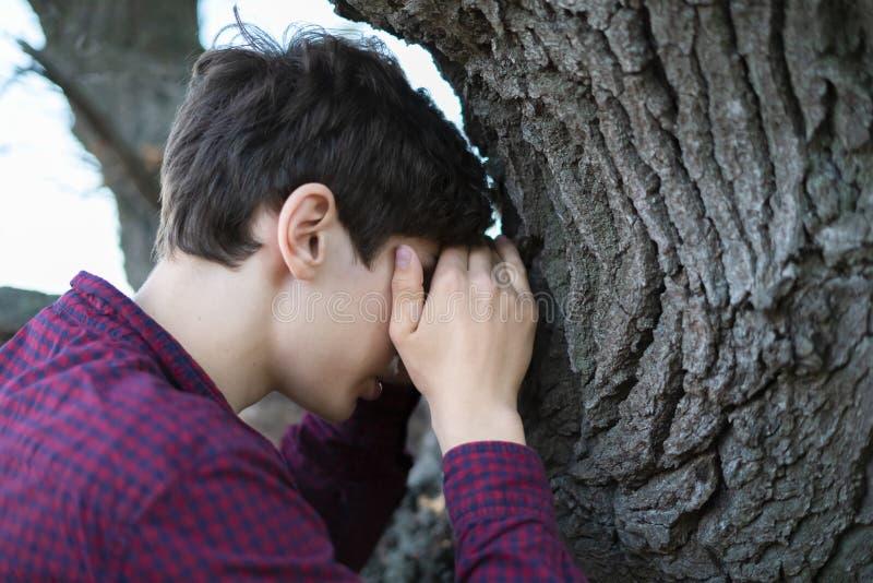 O homem novo conta o jogo do esconde-esconde com olhos fechou f fotografia de stock royalty free