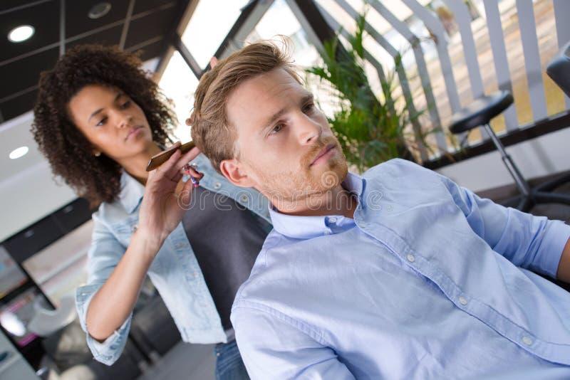 O homem novo corta o cabelo na barbearia bonita fotos de stock