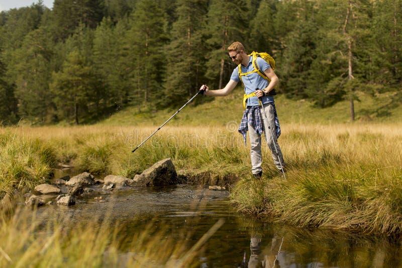 O homem novo cruza um córrego da montanha durante uma caminhada em um dia ensolarado fotos de stock royalty free