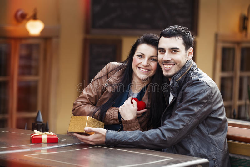 O homem novo dá um presente a uma rapariga no café e nos eles fotografia de stock royalty free