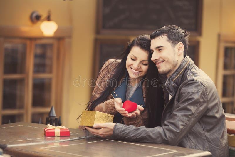 O homem novo dá um presente a uma rapariga no café e nos eles fotos de stock royalty free