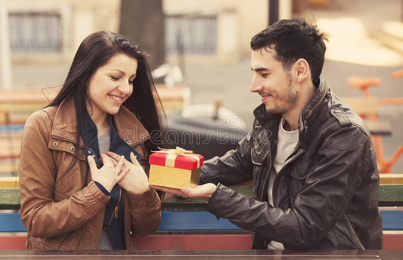O homem novo dá um presente a uma rapariga no café e nos eles imagem de stock