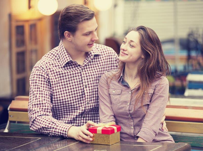 O homem novo dá um presente a uma rapariga no café e nos eles foto de stock royalty free