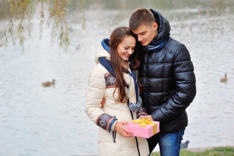 O homem novo dá um presente a uma rapariga no café e nos eles fotos de stock