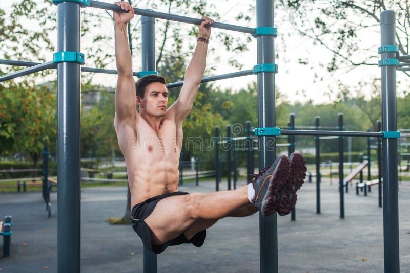 O homem novo da aptidão que faz o pé de suspensão levanta o exercício que dá certo seu Abs no parque imagem de stock