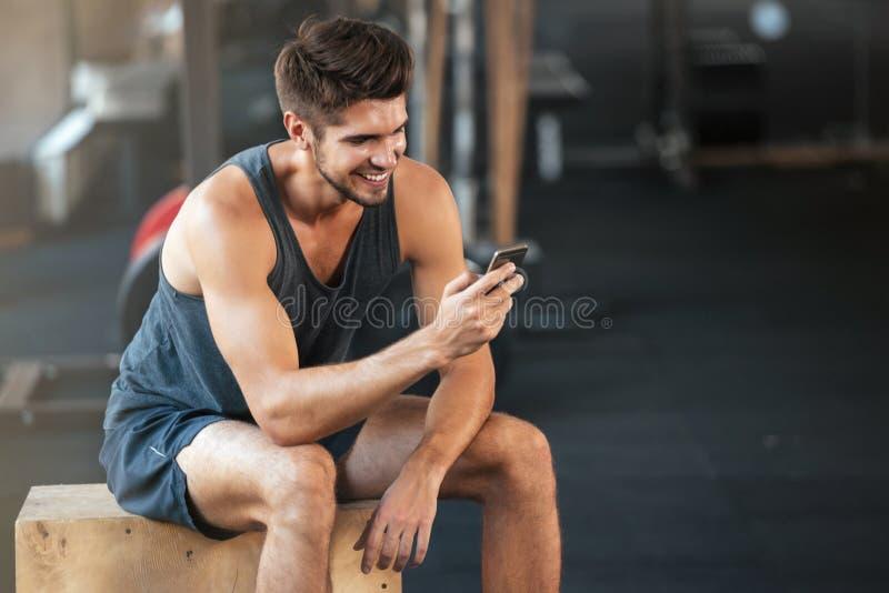 O homem novo da aptidão senta-se na caixa fotografia de stock royalty free