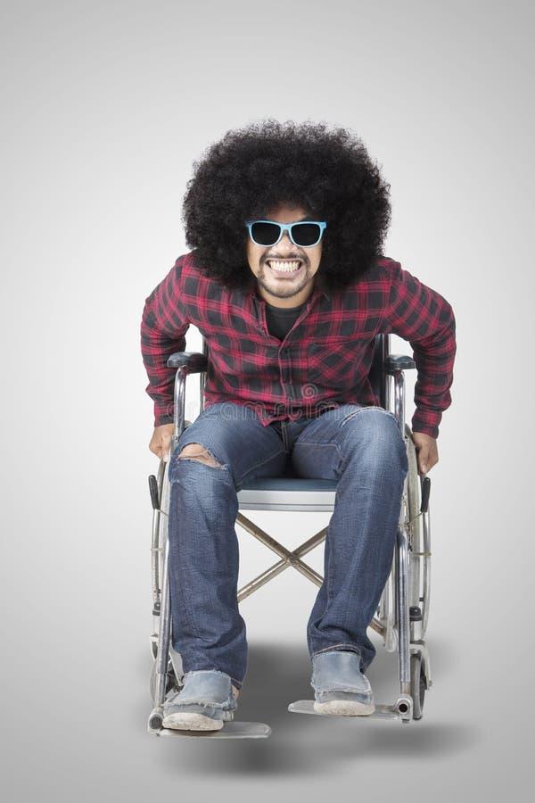 O homem novo deficiente olha feliz em uma cadeira de rodas fotografia de stock