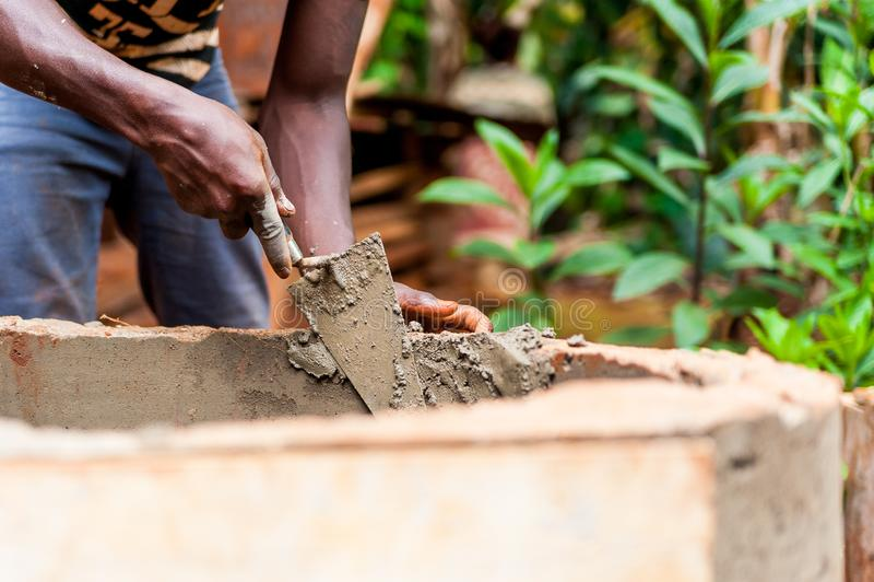 O homem novo do africano negro entrega o trabalho com cimento para construir bem a água na vila de África foto de stock royalty free