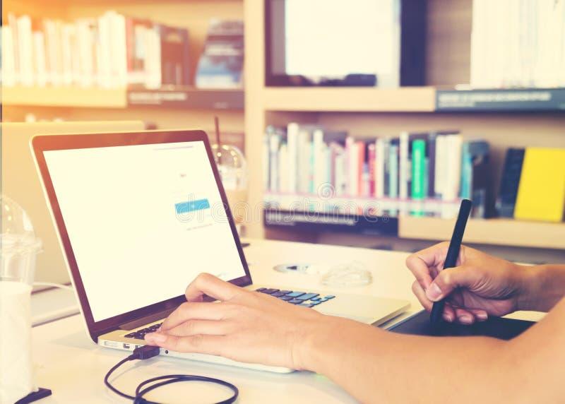 O homem novo do designer gráfico entrega o trabalho ocupado em seu portátil que senta-se na tabela da biblioteca em uma universid fotos de stock royalty free