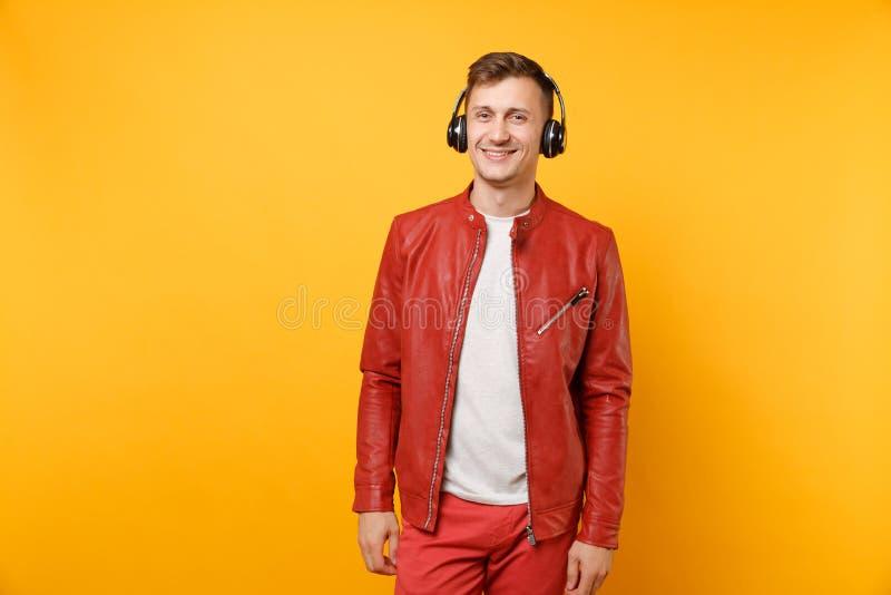 O homem novo do divertimento feliz da moda do retrato no casaco de cabedal vermelho, t-shirt escuta música nos fones de ouvido is fotografia de stock
