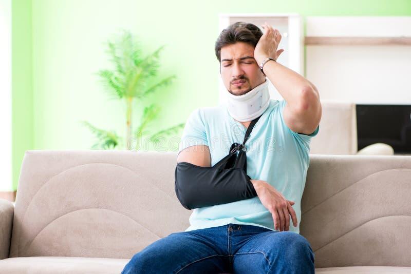 O homem novo do estudante com ferimento do pescoço e de mão que senta-se no sofá fotos de stock