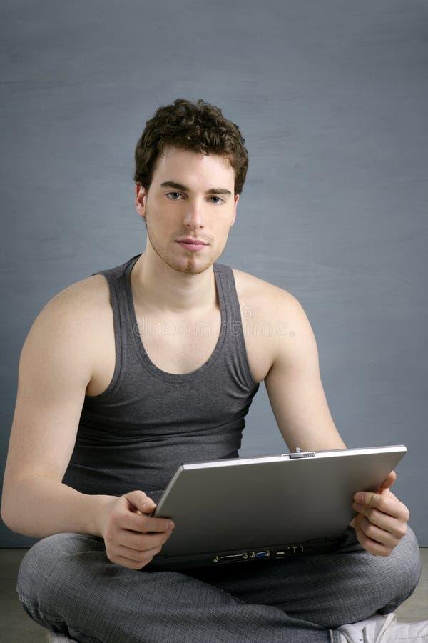 O homem novo do estudante considerável senta o portátil de trabalho fotografia de stock royalty free