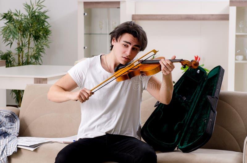 O homem novo do m?sico que pratica jogando o violino em casa imagens de stock royalty free