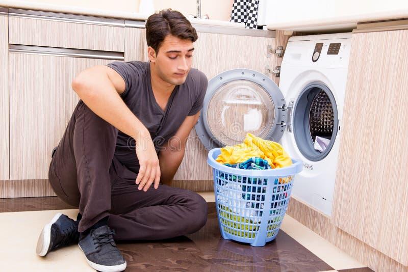 O homem novo do marido que faz a lavanderia em casa fotos de stock