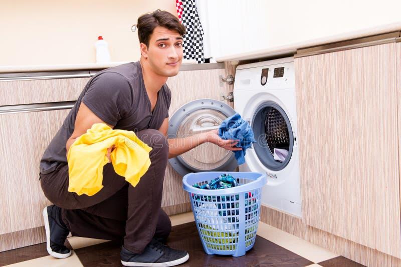 O homem novo do marido que faz a lavanderia em casa imagem de stock royalty free